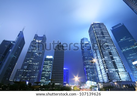 Looking up at the modern office buildings at night in Shanghai