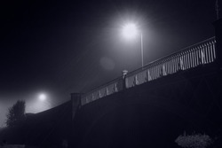 Looking up at the railings on a bridge. Illuminated by street lights. On a atmospheric foggy night.