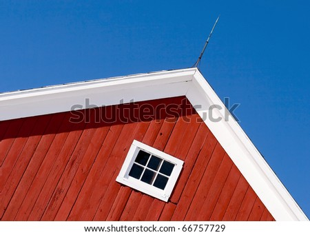 Looking up at the top of a gabled roof on a red barn.