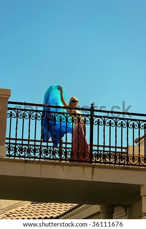 looking up at woman on balcony  wearing a long pink dress holding a blue silk cloth and waving with room for text