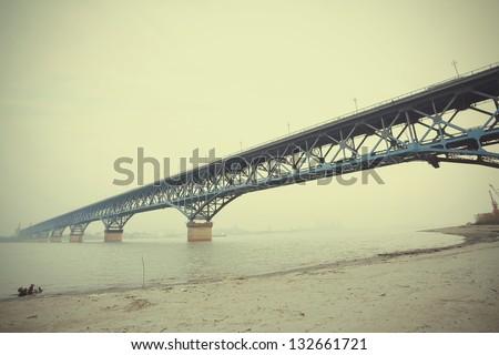 Looking up blue steel structure bridge across the water
