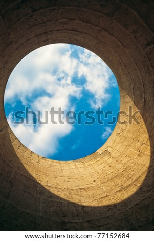 Looking up from the interior of a cooling tower/ chimney showing a blue-white circle of sky resembling our blue planet earth in space.