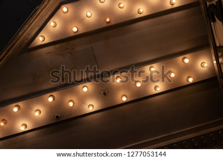 Looking up from the Sidewalk at Many Light Bulbs in a Theater Marquee Overhang Generic #1277053144