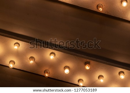 Looking up from the Sidewalk at Many Light Bulbs in a Theater Marquee Overhang Generic #1277053189