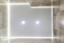 looking up on suspended ceiling with halogen spots lamps and drywall construction in empty room in apartment or house. Stretch ceiling white and complex shape.