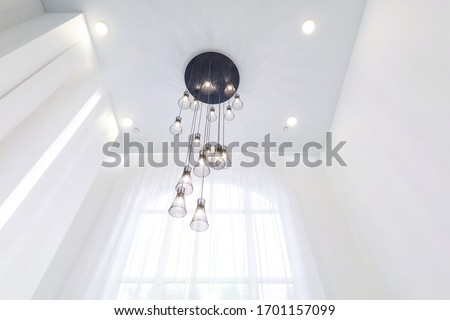 Photo of  looking up on suspended ceiling with halogen spots lamps and drywall construction in empty room in apartment or house. Stretch ceiling white and complex shape.