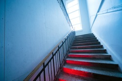 Looking up the scary distorted stairway. Stairs going up with red light on steps