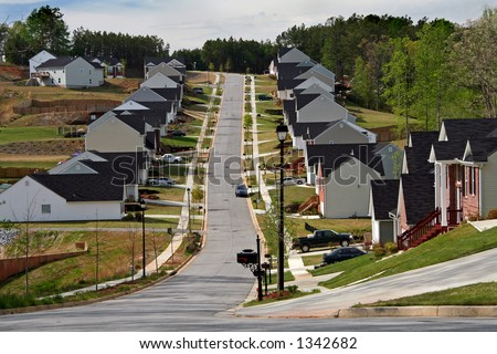 Looking up the street of a neighborhood of midsize homes.