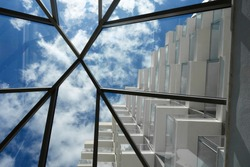 Looking up through a skylight at cloudy blue sky and the balconies of a white, modern building