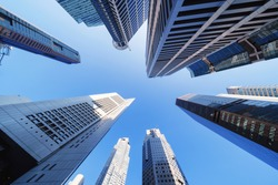 Looking up to high-rise buildings, skyscrapers, architectures in smart city for technology background in Singapore City with blue sky
