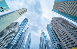 Looking up to high-rise office buildings, skyscrapers, architectures in financial district with blue sky. Smart urban city for business and technology concept background in Downtown Dubai, UAE.