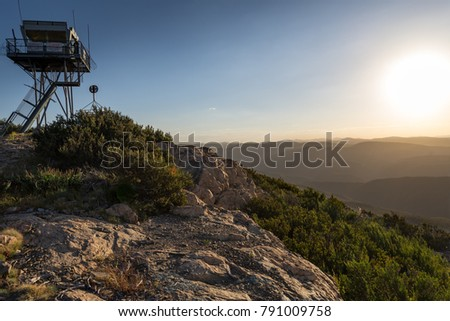 Lookout from Mount Coree view to Brindabella valley ranges at sunset. Sun shine over the ranges with blue sky, rock ledge in the foreground and fire watch tower peering in the background.