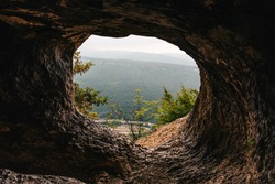 Lookout from tunnel or corridor or hole of cave at mountain peak, toned