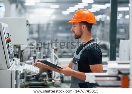 Looks at equipment and makes notes. Industrial worker indoors in factory. Young technician with orange hard hat.