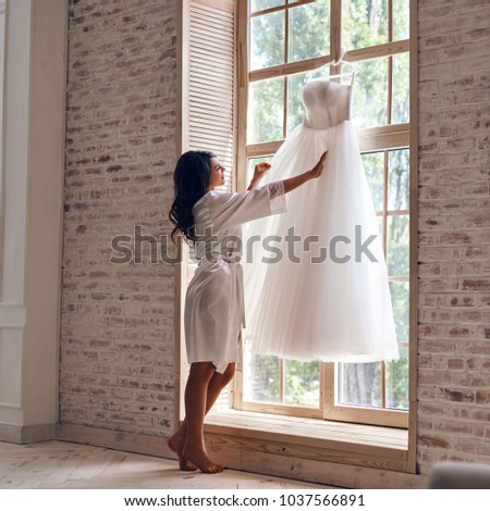 Looks just right. Full length of beautiful young woman in silk bathrobe touching her wedding dress while standing near the window #1037566891