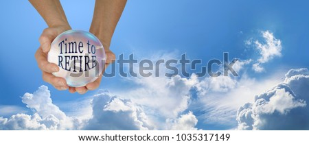 Looks like it is time to retire - Female hands holding a large crystal ball containing the words TIME TO RETIRE against a blue sky and fluffy clouds wide background with copy space