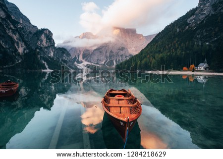 Looks like sun goes down. Wooden boats on the crystal lake with majestic mountain behind. Reflection in the water. Chapel is on the right coast.