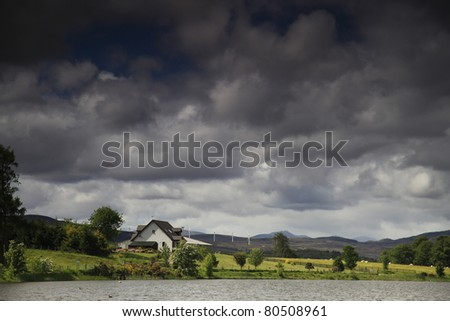 Looming Clouds over a loch in the Scottish Highlands with wind turbines in the distance