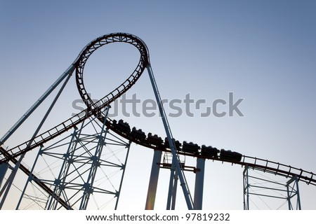 Loop of a roller coaster back lit by the sunset.
