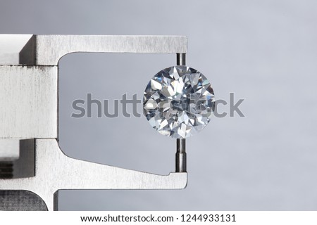 loose big brilliant round diamond is being measure by mm gauge and weight estimator for size