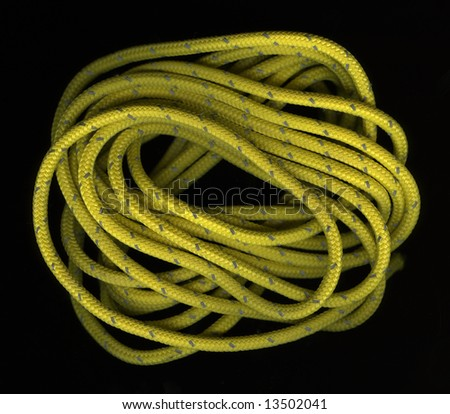 loose coils of yellow, nylon rope wit a reflective, silver thread on black background