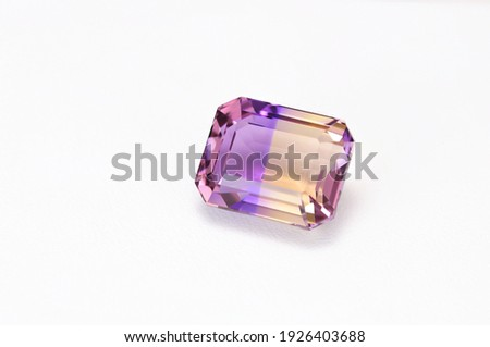 Loose natural bicolor: purple and yellow, Bolivian ametrine emerald cut faceted gemstone on white leather textured background