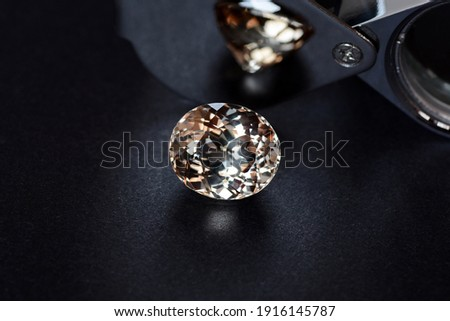 Loose natural light brown color oval faceted topaz gemstone on dark gray background with shades and reflection on mirror surface of jewelers loupe magnifier. Natural day light from window.
