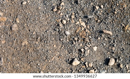 Loose stone aggregate texture featuring large and small stones on a gravel type background.