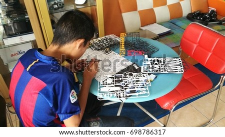 lopburi thailand - august 19 , 2017 : a boy making a model on blue table. #698786317