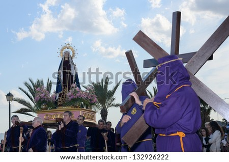 Lorca, Spain - March 22, 2013: Penitential Via Crucis to Calvary with our Lady of Sorrows accompanied with penitents with crosses on his shoulder in Lorca, Spain
