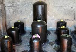 Lord Shiva Linga sculpture arranged in the row for worship at the complex of Brihadeeswarar temple in Thanjavur, Tamilnadu. Black Shiva Linga statues in Hindu temple complex.
