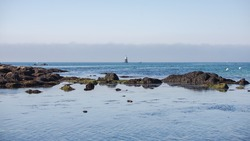 Lorient, Larmor Plage, beach, low tide with lighthouse in sunlight