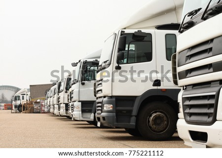 lorries parked up outside a company's car parking area ready to deliver goods to customers