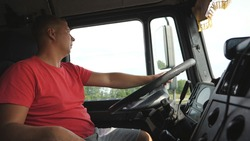 Lorry driver holds arm on a steering wheel and controls truck riding to destination. Man operating a car through countryside at summer day. Trucker driving at country road. Logistics concept. Close up