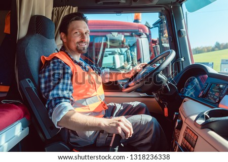 Lorry or truck driver sitting in the cabin of his vehicle driving
