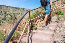 Los Alamos park with man walking up steps of Main Loop trail path in Bandelier National Monument in New Mexico