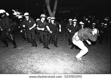 LOS ANGELES, CA - APRIL 29: LAPD advance upon protestor on the south lawn of City Hall while police car burns during night one of the Rodney King Riots on April 29 1992 in Los Angeles, CA.