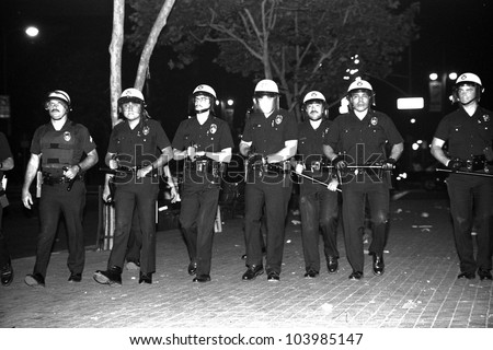LOS ANGELES, CA - APRIL 29: LAPD officers in riot gear advance along the south lawn of City Hall in Downtown LA during night one of the Rodney King Riots on April 29 1992 in Los Angeles, CA.