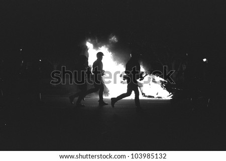 LOS ANGELES, CA - APRIL 29: LAPD officers in riot gear advance past burning police car on night one of the Rodney King Riots on April 29 1992 in Los Angeles, CA.