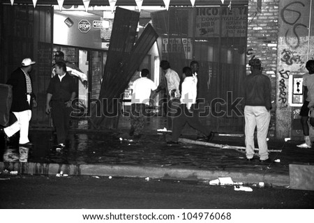 LOS ANGELES, CA - 29 APRIL 1992: Looters tear down storefronts on South Broadway in downtown Los Angeles during night one of the Rodney King Riots on 29 April 1992 in Los Angeles, CA.