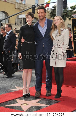 LOS ANGELES, CA - DECEMBER 13, 2012: Hugh Jackman with his Les Miserable co-stars Anne Hathaway (left) & Amanda Seyfried. Jackman was honored with the 2,487th star on the Hollywood Walk of Fame.
