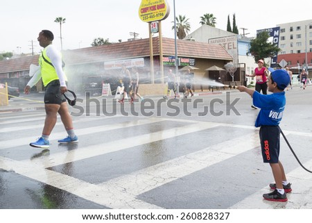 Los Angeles, California, USA - March 15, 2015: Unidentified volunteer boy throwing water in a runner