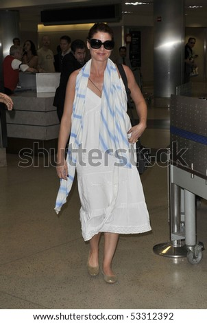 LOS ANGELES - FEBRUARY 14: Actress Debra Messing is seen all smiles in a white dress, scarf and sunglasses as she makes her way thru LAX(Los Angeles Airport)February 14, 2010 in los angeles,california
