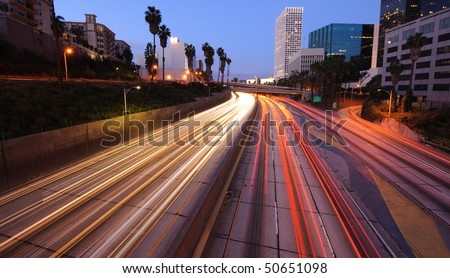 Los Angeles skyline and freeway at twilight - stock photo