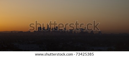 Los Angeles skyline at sunset, showing the large buildings of city downtown with a red sky behind, California, USA
