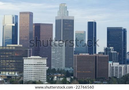 Los Angeles skyline in daylight against blue sky.