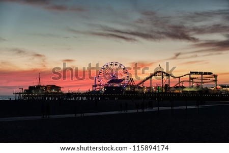 LOS ANGELES, USA - SEPTEMBER 22: Santa Monica Pier at dusk on September 22, 2012 in LA. The pier is a more than hundred-year-old historic landmark that contains Pacific Park, an amusement park.