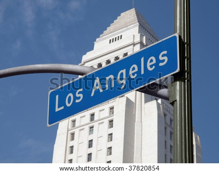 Los Angles street sign with iconic City Hall in background.