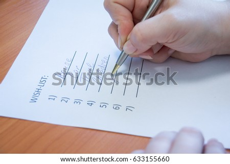 lose up of female hand writing her wish list with pen. business and happiness family concept. Wishes must come true #633155660
