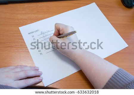 lose up of female hand writing her wish list with pen. business and happiness family concept. Wishes must come true #633632018